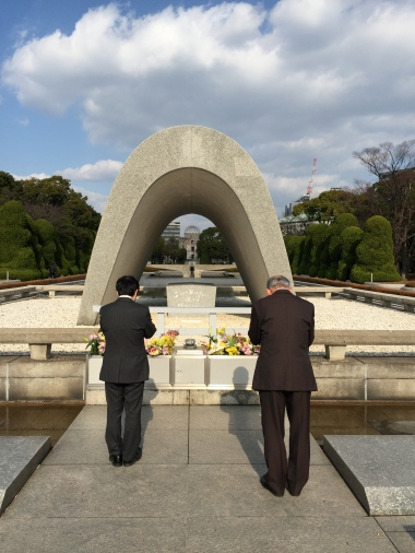 Two men praying at Hiroshima Memorial Park